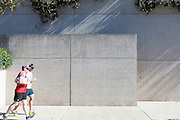 Two men jogging past Queensland Art Gallery, Brisbane, Australia