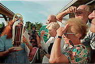 DADE CITY, FLORIDA: Pilgrims perform the sign of the cross as a statue of the Virgin Mary passes by at the home of Vimer Nagun, a teenager who claimed to have apparitions of the Virgin Mary. The small statue is one of several that pilgrims claimed wept tears of oil.  (Photo by Robert Falcetti). .