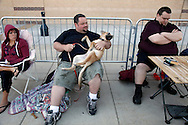 "Aaron Donoho (L) holding his dog Mina and Tony Carloni (R) wait in line at an open casting call for season 11 of ""The Biggest Loser"" television show in Broomfield, Colorado July 17, 2010.  Over 600 people applied for a chance to be on the show and win $250,000.  REUTERS/Rick Wilking (UNITED STATES)"