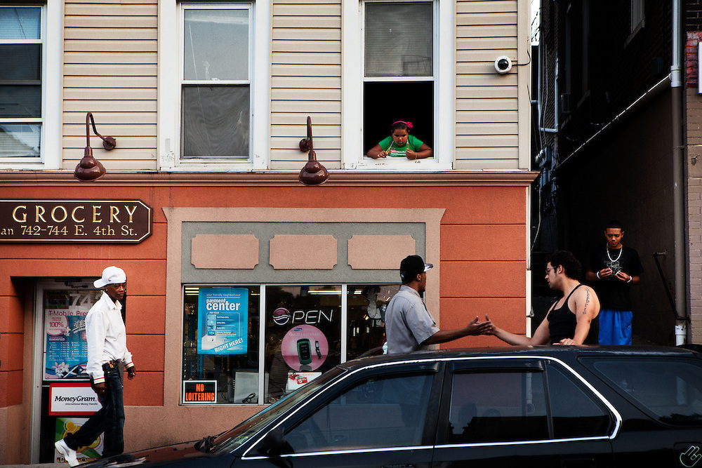 BETHLEHEM, PA – JUNE 18, 2011: Jose Marin, 22, greets a friend outside Nieves Grocery on 4th Street in Bethlehem as Angel Peres, 19, joins him from the alley. Like many Hispanics in Bethlehem, Marin immigrated to Pennsylvania's Lehigh Valley from Puerto Rico eight months earlier.<br />