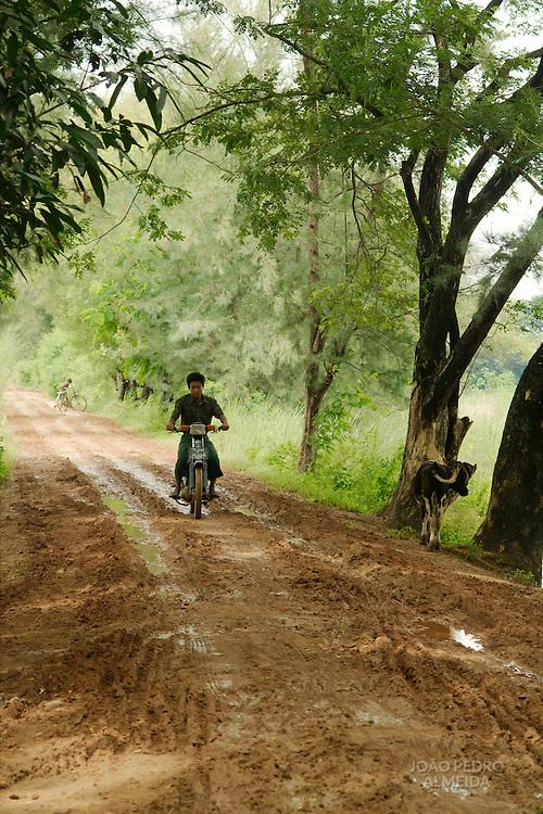 Burmese man riding a bike at rural, muddy road outside Mandalay