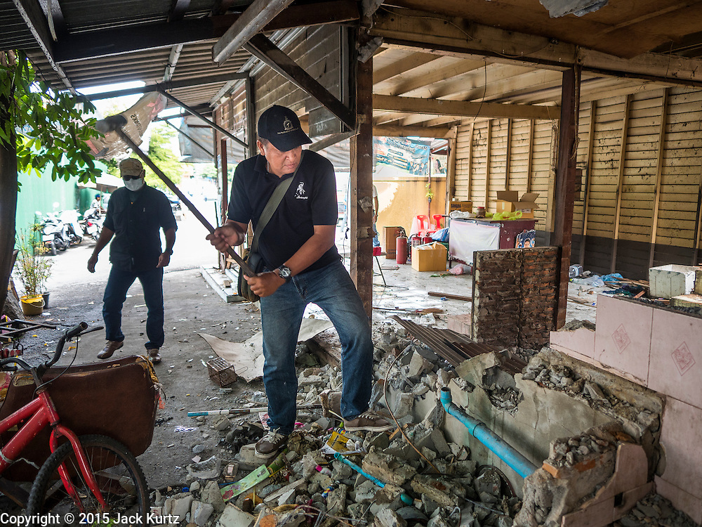 11 SEPTEMBER 2015 - BANGKOK, THAILAND:  Demolition workers use a sledge hammer to dismantle Chaiyasit Kittiwanitchapant's home in front of Wat Kalayanamit. Authorities started to destroy 54 homes in front of Wat Kalayanamit, a historic Buddhist temple on the Chao Phraya River in the Thonburi section of Bangkok. Government officials, protected by police, seized the house of Chaiyasit Kittiwanitchapant, a Kanlayanamit community leader, who has led protests against the temple's abbot for trying to evict community members whose houses are located around the temple. Work crews went into Chaiyasit's home and took it apart piece by piece. The abbot of the temple said he was evicting the residents, who have lived on the temple grounds for generations, because their homes are unsafe and because he wants to improve the temple grounds. The evictions are a part of a Bangkok trend, especially along the Chao Phraya River and BTS light rail lines, of low income people being evicted from their long time homes to make way for urban renewal.        PHOTO BY JACK KURTZ