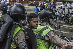 June 19, 2017 - Caracas, Distrito Capital, Venezuela - Police officers detain an anti-government demonstrator in Caracas, Venezuela, Monday, June 19, 2017. Nearly 70 people have died, hundreds more have been injured and thousands have been detained in months of almost daily protests demanding new elections as the nation battles triple-digit inflation, crippling food and medical shortages and rising crime. (Credit Image: © Marcos Canizares/VW Pics via ZUMA Wire)
