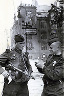 Soviet Russian soldiers light a cigarette while patrolling Berlin after its fall at the end of World War II. One soldier is carrying a Soviet 7.62mm PPSH submachine gun. This image is from the archive of a photojournalist who photographed WWII for the Red Army.