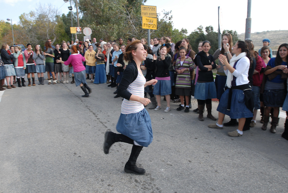 Young Jewish settler girls dancing while blocking the entrance road to the Jewish settlement of Kdumim in the West Bank, expecting inspectors of the Civil Administration on 03 Dec, 2009.