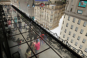 street scene with people walking reflected in mirrored roof Madrid Gran Via