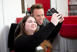 Olly Murs takes a selfie with a young girl during a music workshop with patients for the Teenage Cancer Trust at the Royal Albert Hall, London.
