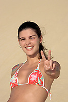 beautiful smiling bikini dressed young brazilian  woman in the wind of the sand dune of jericoacoara ceara state near fortaleza making sign of victory with her fingers