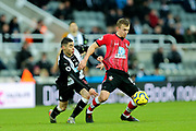 James Ward-Prowse (#16) of Southampton holds off the challenge of Miguel Almiron (#24) of Newcastle United during the Premier League match between Newcastle United and Southampton at St. James's Park, Newcastle, England on 8 December 2019.