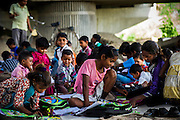 8th April 2013, Shakarpur, New Delhi, India.  L-R foreground: Mamta, Savitha Kumari (12, centre) and Kunti study at a makeshift school under a metro bridge near the Yamuna Bank Metro station in Shakarpur, New Delhi, India on the 8th April 2013. <br /> <br /> Rajesh Kumar Sharma (born 01/02/1970), started this makeshift school in 2011. Six mornings a week he teaches underprivileged children for three hours while his younger brother replaces him at his general store in Shakarpur. His students are children of labourers, rickshaw-pullers and farm workers. This is the 3rd site he has used to teach under privileged children in the city, he began in 1997.<br /> PHOTOGRAPH BY AND COPYRIGHT OF SIMON DE TREY-WHITE<br /> + 91 98103 99809<br /> email: simon@simondetreywhite.com<br /> photographer in delhi<br /> journalist