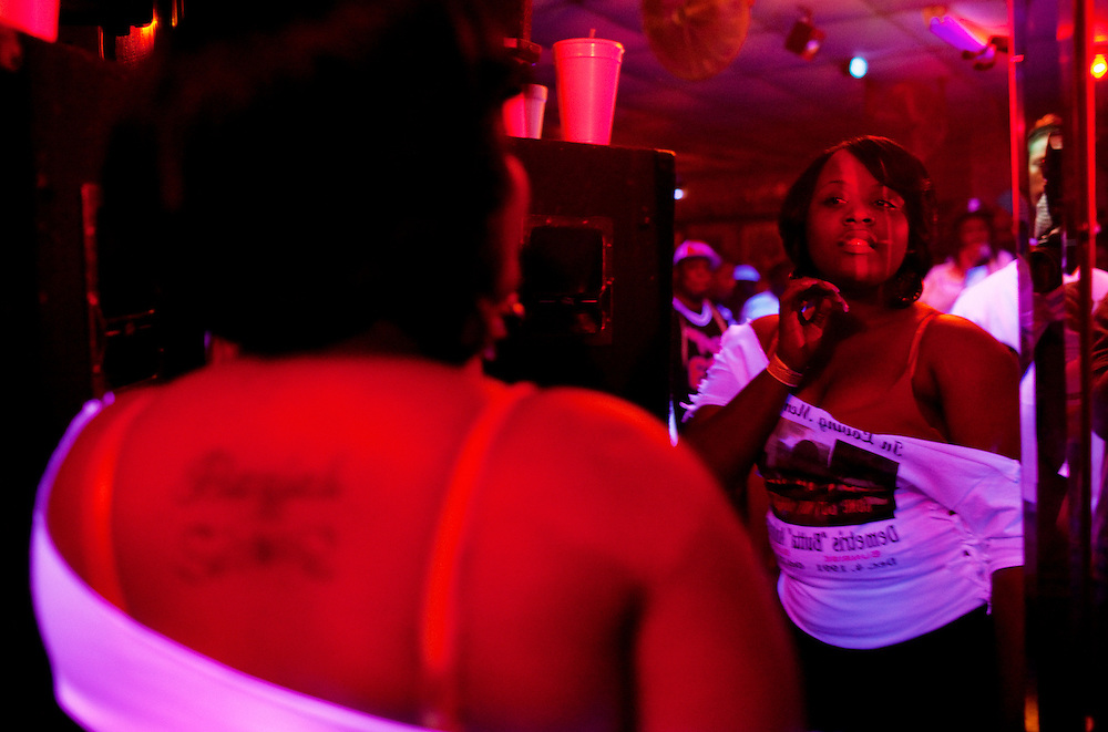 "A young woman checks herself out in the mirror at Scruples Sports Bar in Itta Bena, Mississippi where friends and family of Demetrius ""Butta"" Anderson, 18, came to party into the night after Butta's funeral in the Baptist Town neighborhood of Greenwood, Mississippi on Friday, November 5, 2010. Butta was shot and killed on October 27, 2010."
