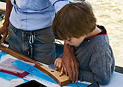 Boy making his first strum stick with Andy Mackie at an Andy Mackie Music Foundation event during the 2009 American Fiddle Tunes Festival at Fort Worden in Port Townsend, Washington.