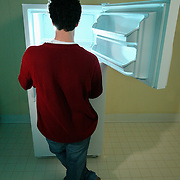 A man looks into a freezer while cold smoke pours out of the appliance.