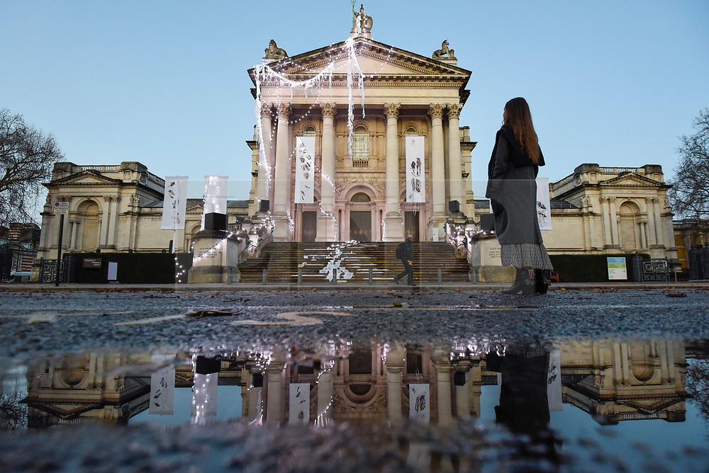 © Licensed to London News Pictures. 29/11/2019. LONDON, UK.  A passerr by views Tate Britain's new Winter Commission which has just been unveiled.  British artist Anne Hardy has transformed Tate Britain's facade into a marooned temple celebrating the earth, tides and winter solstice.  The installation will be on display until 26 January 2020.  Photo credit: Stephen Chung/LNP