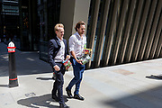 Beneath new architecture, City businessmen walk along Bevis Marks in the City of London, the capital's financial district, on 17th June 2019, in London, England.