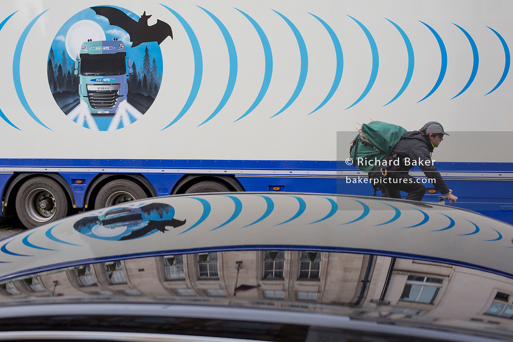 The design on the side of an HGV for the rehearsal studio company 'Fly By Nite' and a passing cyclist in Great Marlborough Street, on 5th March 2019, in London, England.