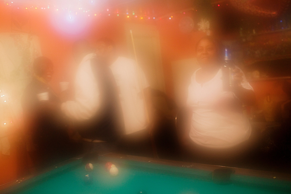 Men and women dance and play pool at Odessa Nicks' one-room club in the Baptist Town neighborhood of Greenwood, Mississippi on February 18, 2011. A layer of fog covers the lens after entering the air-conditioned room from the humid May evening outside.