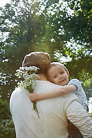 Father and daughter (5-6) embracing in countryside daughter carrying bunch of flowers