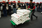 "A SanDisk employee pushes a cart loaded with bags of rice during the Stop Hunger Now Foundation's ""Mayday, Mayday"" food-packing event at SanDisk Corporation in Milpitas, California, on May 13, 2014. (Stan Olszewski/SOSKIphoto)"