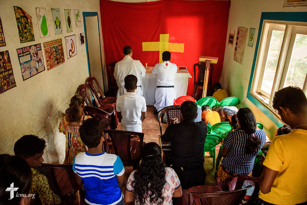 The Rev. P. Gnanakumar kneels and prays as he leads worship on the Eila rubber plantation in the Sabaragamuwa Province of Sri Lanka on Sunday, Jan. 21, 2018. Next to him is the Rev. Steven Mahlburg, LCMS career missionary to Sri Lanka. LCMS Communications/Erik M. Lunsford
