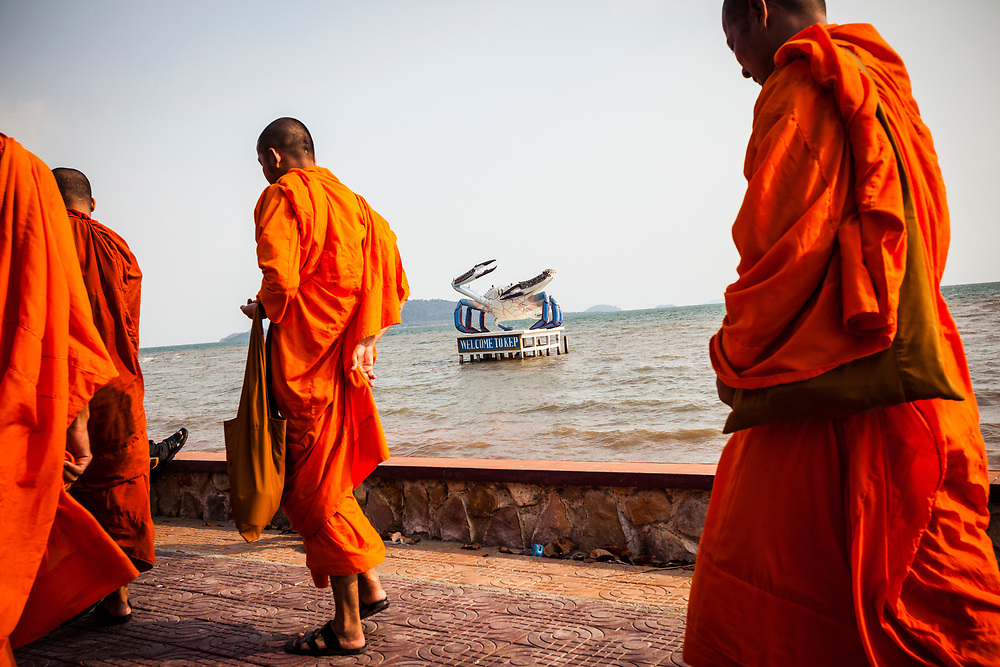 Saffron-robed monks walk along the waterfront in Kep, Cambodia.