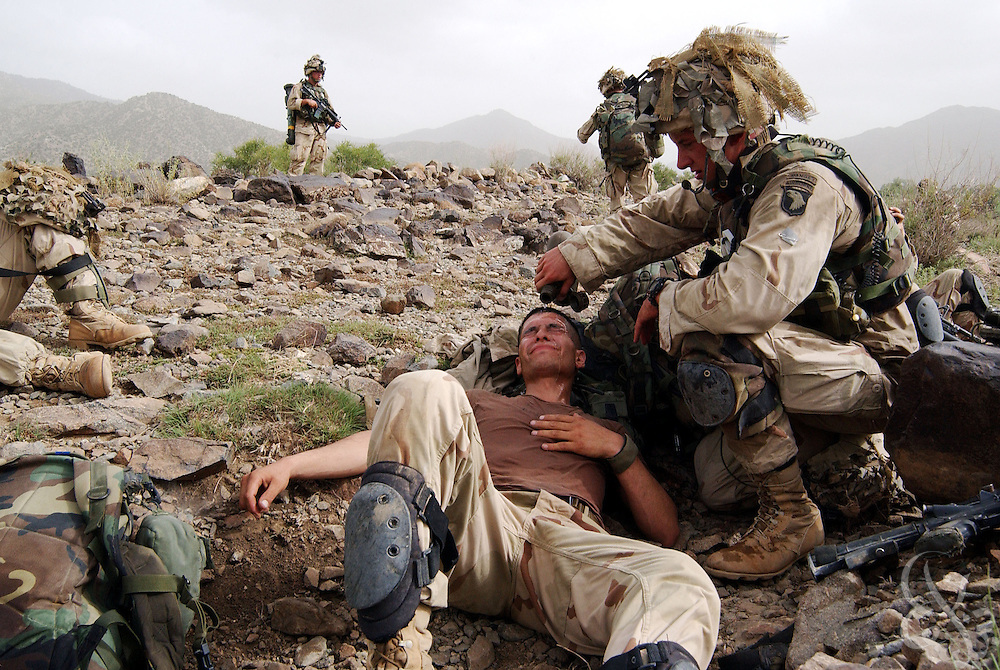 "A US Army 101st Airborne 3-187 ""Bravo"" company medic pours cold water over the face of a dehydrated soldier overcome by heat and exhaustion while conducting a 23 July, 2002 sensitive site exploitation (SSE) mission in the town of Narizah in Southeastern Afghanistan . The three day mission, intended to deny sanctuary to Al Qaida and Taliban fighters in villages along the Pakistan-Afghanistan border resulted in the recovery of several weapons caches and one Afghan detained for questioning."