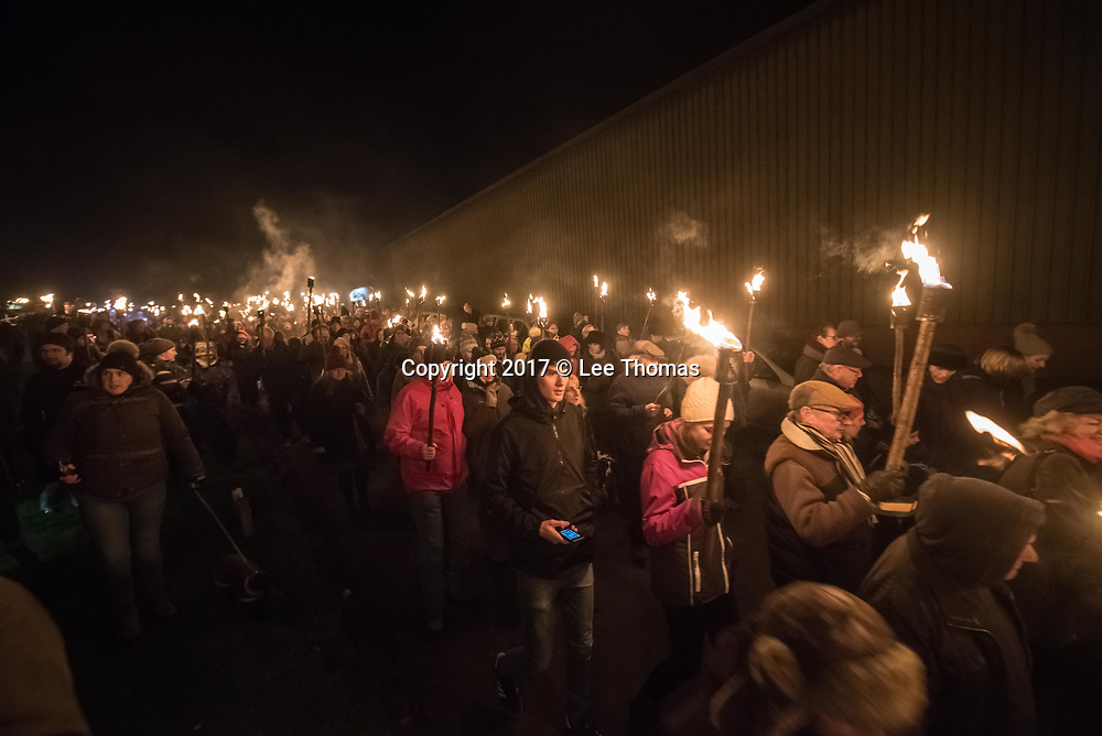 Much Marcle, Herefordshire, UK. 6th January 2018. Pictured:  Hundreds of people hold their lit torches  above their heads as they march to the orchard. / Hundreds of people both young and old gathered at the Westons Cider Mill and adjoining orchard to take part in the traditional Wassail ceremony. The event at Much Marcle in Herefordshire was attended by the Silurian morris side who entertained the crowd with witty repartee, raucous dancing and music. According to their website, the true origins of blackened faces are lost to history, but are widely believed to be simply a form of disguise, possibly to overcome the oppressive anti-begging laws of the 17th century, and the eternal embarrassment of being a morris man. The orchard-visiting wassail refers to the ancient custom of visiting orchards in cider-producing regions of England, reciting incantations and singing to the trees to promote a good harvest for the coming year. // Lee Thomas, Tel. 07784142973. Email: leepthomas@gmail.com  www.leept.co.uk (0000635435)