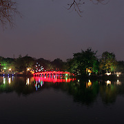 The wooden red-painted Huc Bridge at night time. Also know as the Morning Sunlight Bridge and The Red Bridge which connects Jade Island to the shore of Hoan Kiem Lake, in the centre of Hanoi, Vietnam, 17th March 2012. Photo Tim Clayton