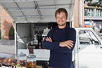Portrait of young man with arms crossed standing against mobile coffee shop