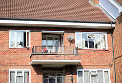 © Licensed to London News Pictures. 15/09/2016. London, UK. A flat (top with red chair on balcony) which was the scene of a double shooting in a block of flats in East Finchley. Police were called by London Ambulance Service at 06:25hrs this morning to reports of two people injured at an address in north London. A man and a woman were found with gunshot injuries. Both were pronounced dead at the scene. Photo credit: Ben Cawthra/LNP