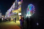 Nederland, The Netherlands, Nijmegen, 19-7-2016 Recreatie, ontspanning, cultuur, dans, theater en muziek in de binnenstad. Het casino op de  Waalkade met een spiegeling van het reuzenrad. Onlosmakelijk met de vierdaagse, 4daagse, zijn in Nijmegen de vierdaagse feesten, de zomerfeesten. Talrijke podia staat een keur aan artiesten, voor elk wat wils. Een week lang elke avond komen ruim honderdduizend bezoekers naar de stad. De politie heeft inmiddels grote ervaring met het spreiden van de mensen, het zgn. crowd control. De vierdaagsefeesten zijn het grootste evenement van Nederland en verbonden met de wandelvierdaagse. Hier het podium op de Waalkade Foto: Flip Franssen