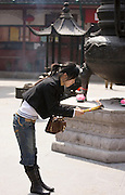 Worshipper burning incense at the Jade Buddha Temple, Shanghai, China