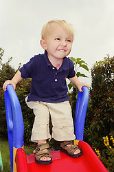 Young boy standing at top of slide in garden,