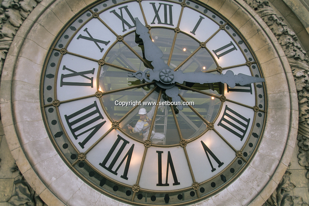 France. Paris. Man Cleaning Musee d'Orsay Clock