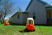 Brightly coloured yellow and red plastic children's cars on the lawn of a wooden house, USA, 2000's