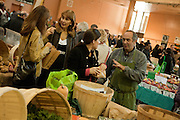 A male vendor at the St. Lawrence Farmer's Market in Toronto, giving a woman a recipe as two women compare culinary notes in the background.