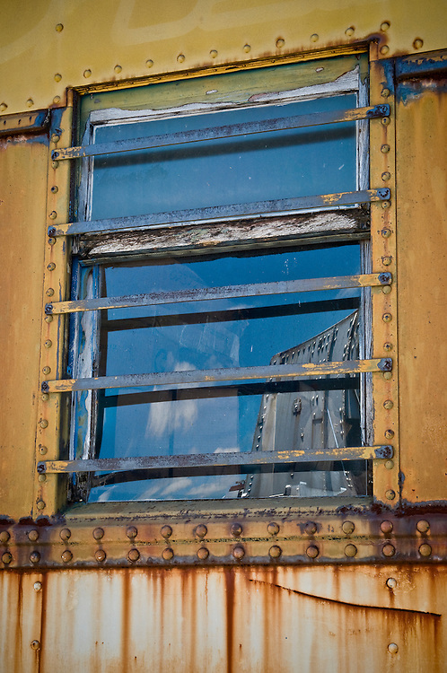 Rusted window of an old and abandoned train wagon.