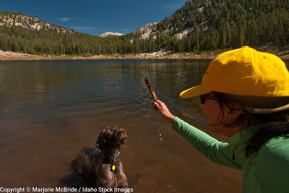 Woman plays fetch with dog at Mill Creek Lake while hiking in the Lemhi Mountain range during summer.  Idaho. Model Release