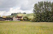 View over fields and farmhouse to the White Horse figure on the chalk scarp slope on Cherhill Down, Wiltshire, England