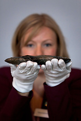© Licensed to London News Pictures. 19/07/2012. LONDON, UK. Nicola Kalimeris, a Museum of London press officer, holds a 6000 year old flint axe head at the museum today (19/0712).  The axe head is one of many artefacts that were unearthed by archaeologists ahead of the construction of the Olympic Park in East London which included findings from the Neolithic, Roman and Bronze Ages. Photo credit: Matt Cetti-Roberts/LNP