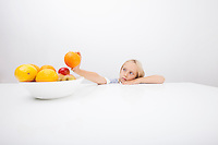 Little girl looking at orange while leaning on table