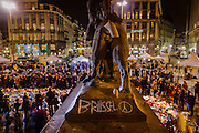 Brussels Belgium 25 march 2016. People gathered in front de Beurs, the  former Brussels stock exchange, to remember the victims of the terrorist attacks by singing, waving flags, and laying flowers and candles on the street, statue backside of lion with peace sign and a sea of flowers and candles