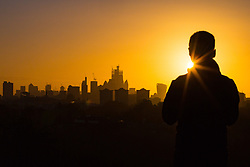 A man admires the glorious sunrise as day breaks over London's skyline, seen from Primrose Hill, to the north of the city. London, November 13 2018.