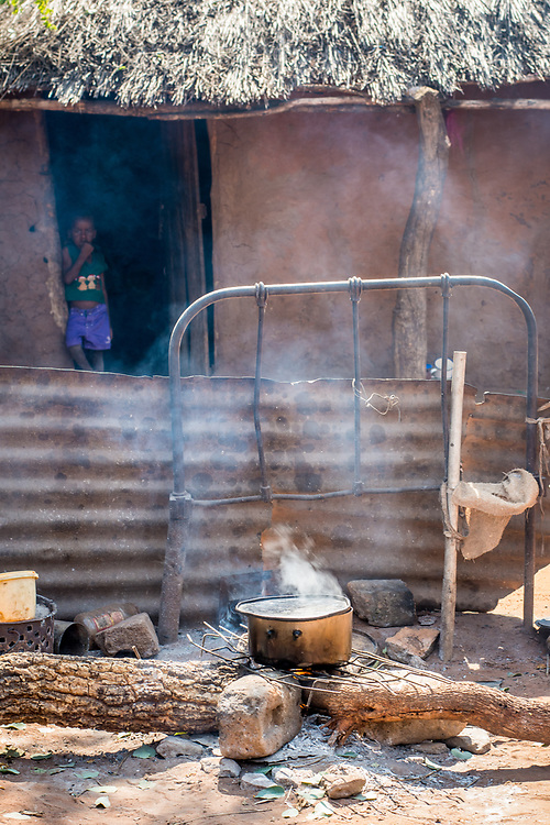 Metal cooking pot sits on grate on top of campfire with thatched hut behind it, Mukuni Village, Zambia
