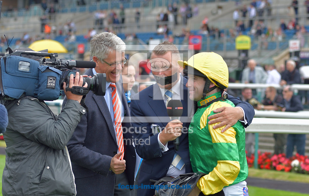 Horse racing presenter Matt Chapman with his mouth covered by gaffer tape to raise money for Voice Of Racing Charity day interviews jockey Robert Winston after winning race 1 on Eirene at the 188 Bet Summer Afternoon meeting at Doncaster Racecourse, Doncaster<br /> Picture by Martin Lynch/Focus Images Ltd 07501333150<br /> 30/06/2017