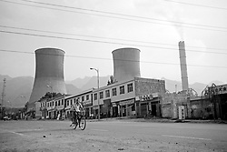 China, Dengfeng, 2003. A factory worker heads home down a virtually abandoned street. Electricity cooling towers loom over more and more towns each year as China searches for ways to generate power..