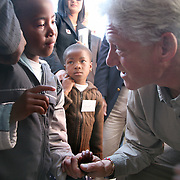 July 13, 2006 - President Clinton croutches down in a crowd of people to speak with a little girl at the antiretroviral treatment center, Karabong Clinic, at Mafeteng Hospital in Lesotho. Karabong clinic is the second largest government-run treatment facility in Lesotho with 1200 patients receiving ART. Photo by Evelyn Hockstein