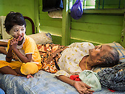 02 JUNE 2015 - KULAI, JOHORE, MALAYSIA:  ASMA, 90 years old, a Rohingya refugee from Myanmar with one of her great grandchildren in their home in Kulai. They came to Malaysia on a boat with 50 members of their extended family. They paid traffickers 250,000 Malaysian Ringgits (about $65,000 US) to bring them to Malaysia via traffickers' camps in Thailand. The UN says the Rohingya, a Muslim minority in western Myanmar, are the most persecuted ethnic minority in the world. The government of Myanmar insists the Rohingya are illegal immigrants from Bangladesh and has refused to grant them citizenship. Most of the Rohingya in Myanmar have been confined to Internal Displaced Persons camp in Rakhine state, bordering Bangladesh. Thousands of Rohingya have fled Myanmar and settled in Malaysia. Most fled on small fishing trawlers. There are about 1,500 Rohingya in the town of Kulai, in the Malaysian state of Johore. Only about 500 of them have been granted official refugee status by the UN High Commissioner for Refugees. The rest live under the radar, relying on gifts from their community and taking menial jobs to make ends meet. They face harassment from Malaysian police who, the Rohingya say, extort bribes from them.    PHOTO BY JACK KURTZ