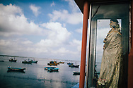 A statue of a saint watches over fishermen boats in Jaffna, Sri Lanka, Asia