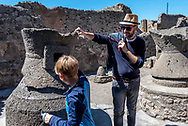 POMPEII, ITALY - APRIL 7, 2018:  A Pompeii tour guide challenges a nine-year-old visitor to turn the still-functional mill stone in an ancient bakery. More than thirty bakeries have been found in the ruins of Pompeii, including one with carbonized loaves of bread in an oven.